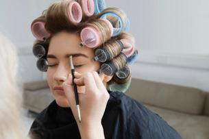 Model in Hair Curlers Having Makeup Appliedの写真素材 [FYI03645681]