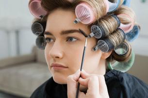 Model in Hair Curlers Having Makeup Appliedの写真素材 [FYI03645682]