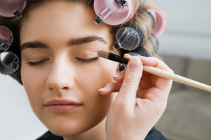 Model in Hair Curlers Having Makeup Appliedの写真素材 [FYI03645683]