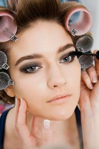 Model in Hair Curlers Having Makeup Appliedの写真素材 [FYI03645688]