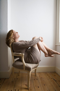 Semi dress woman relaxing on old fashioned chairの写真素材 [FYI03645858]