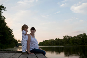 Pregnant Mother And Daughter Sitting On Jetty In Eveningの写真素材 [FYI03645880]