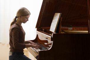 Girl (13-15) playing pianoの写真素材 [FYI03645923]