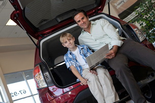 Low angle view of father and son sitting in carの写真素材 [FYI03645956]