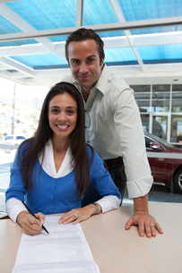 Portrait of woman signing car contract with husband standingの写真素材 [FYI03645976]