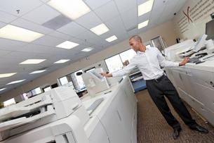 Man working in printing press between two cash register machの写真素材 [FYI03645983]
