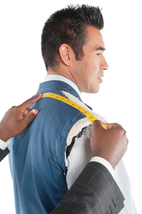 Profile view of man getting measured by tailorの写真素材 [FYI03646036]