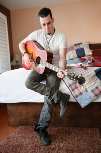 Handsome mid-adult man playing guitarの写真素材 [FYI03646111]