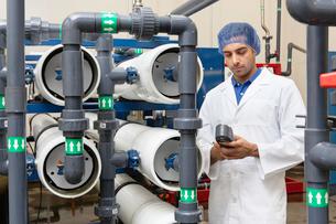 Worker holding an equipment in bottling plantの写真素材 [FYI03646116]