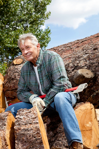 Senior man sitting on wood logs with an axeの写真素材 [FYI03646128]