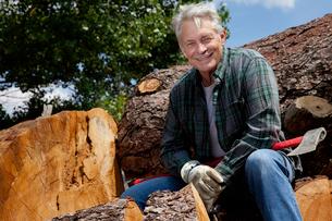 Smiling senior man sitting on logsの写真素材 [FYI03646134]