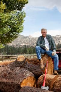 Man sitting on chopped tree trunkの写真素材 [FYI03646136]