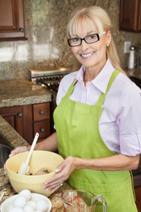 Portrait of a happy senior woman preparing food in kitchenの写真素材 [FYI03646200]