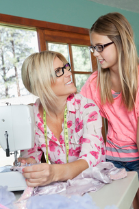 Mature mother looking at daughter while sewing clothの写真素材 [FYI03646201]