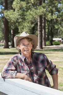 Mature man wearing cowboy hat leaning on wooden slabの写真素材 [FYI03646215]