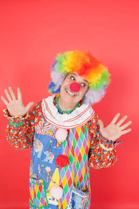 Funny clown with arms raised looking away against colored baの写真素材 [FYI03646287]