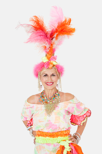 Portrait of happy senior woman in Brazilian outfit over grayの写真素材 [FYI03646298]