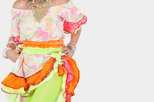 Midsection of senior woman in Brazilian costume over gray baの写真素材 [FYI03646300]