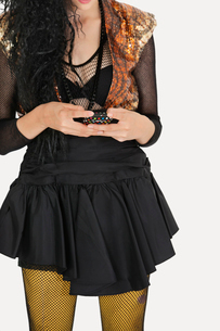 Midsection of young Goth woman text messaging on cell phoneの写真素材 [FYI03646310]