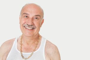 Portrait of cheerful senior man in vest over gray backgroundの写真素材 [FYI03646314]