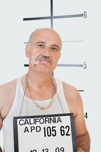 Mug shot of senior gangster smoking cigaretteの写真素材 [FYI03646318]