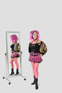 Portrait of senior female punk standing by mirror over grayの写真素材 [FYI03646325]