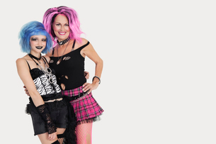 Portrait of punk females standing with arms around over grayの写真素材 [FYI03646327]
