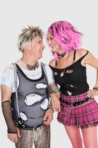 Happy senior punk couple looking at each other over gray bacの写真素材 [FYI03646336]