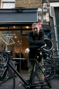 Portrait of mid adult man standing outside cycle shopの写真素材 [FYI03646342]