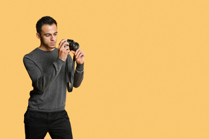 confident young man with digital camera over colored backgroの写真素材 [FYI03646356]