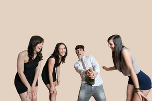 Young friends opening champagne bottle over colored backgrouの写真素材 [FYI03646391]