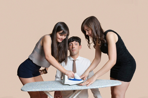 Young women ironing shocked man's tie over colored backgrounの写真素材 [FYI03646396]