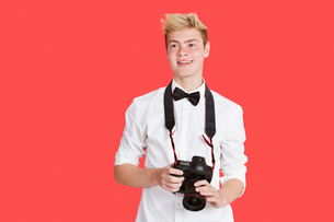 Handsome young man with digital camera over red backgroundの写真素材 [FYI03646406]