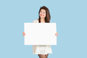 Portrait of a beautiful young woman holding blank cardboardの写真素材 [FYI03646407]