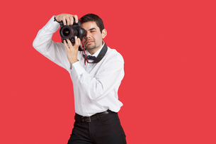Mixed race man taking picture with digital camera over red bの写真素材 [FYI03646409]