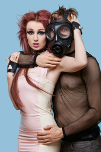 Portrait of young man in gas mask embracing funky woman overの写真素材 [FYI03646426]