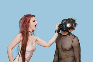Funky young woman slapping man in gas mask over blue backgroの写真素材 [FYI03646427]
