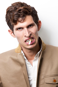Portrait of angry young man smoking over white backgroundの写真素材 [FYI03646436]