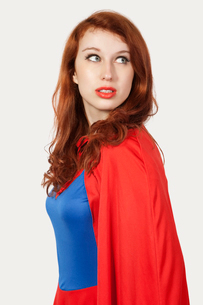 Young woman in superhero costume looking away against gray bの写真素材 [FYI03646447]