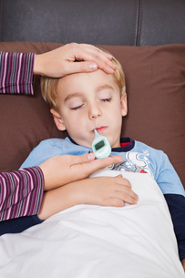 Mother checking unwell little boy's temperature with thermomの写真素材 [FYI03646457]