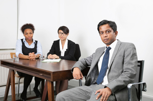 Portrait of Asian male with female colleagues in backgroundの写真素材 [FYI03646461]