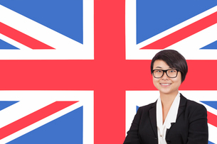 Portrait of young businesswoman smiling over British flagの写真素材 [FYI03646467]