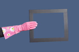 Hand in rubber gloves holding frame over blue backgroundの写真素材 [FYI03646473]