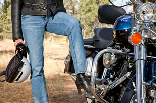 Womans leg rests on motorcycle foot restの写真素材 [FYI03646512]