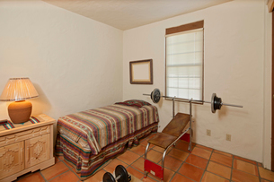 Small single bedroom with bench press and weightsの写真素材 [FYI03646560]