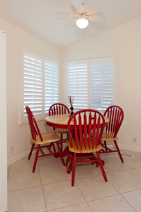 Wooden dining table with red chairsの写真素材 [FYI03646646]
