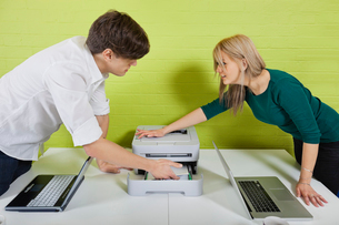 Side view of young businesspeople setting up printer with laの写真素材 [FYI03646665]