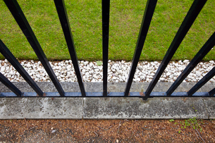 Iron fence, grass and pebblesの写真素材 [FYI03646863]