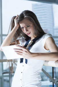 Shocked businesswoman reading tablet deviceの写真素材 [FYI03646869]