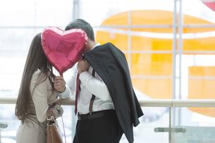Man and woman kiss behind heart shaped balloonの写真素材 [FYI03646890]